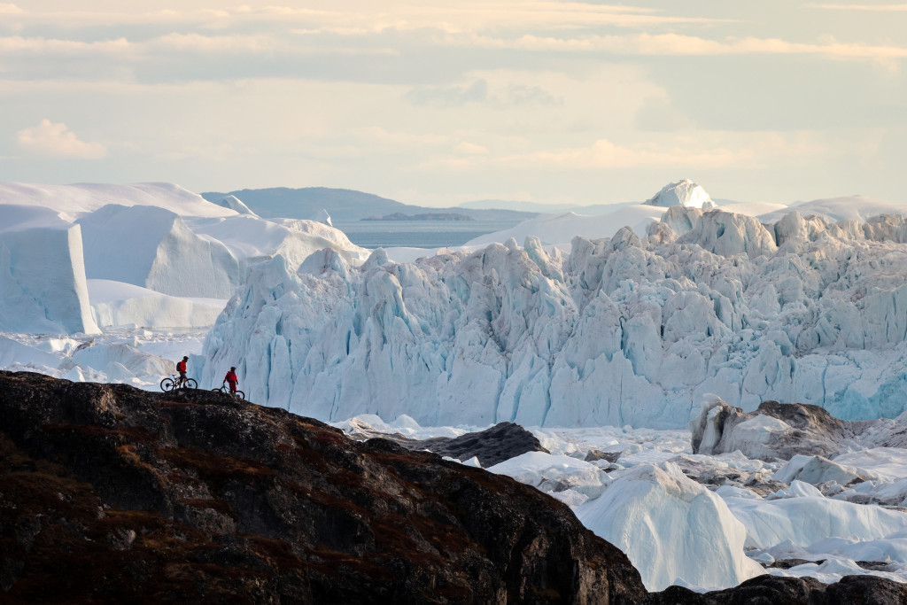 Two men on mountainbikes in fron of a creeping glacier in Greenland.